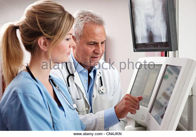 Doctors looking at screens - Stock Image
