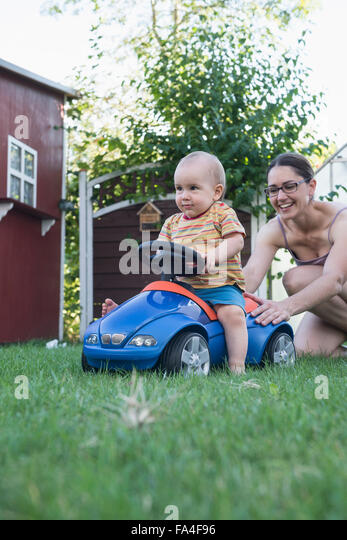 Baby boy riding on toy car with his mother pushing it from behind, Munich, Bavaria, Germany - Stock Image