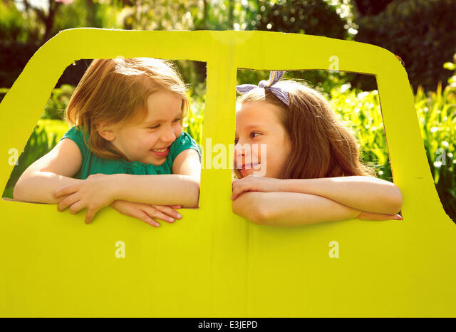 Young Girls Leaning out of Cardboard Car Window - Stock Image
