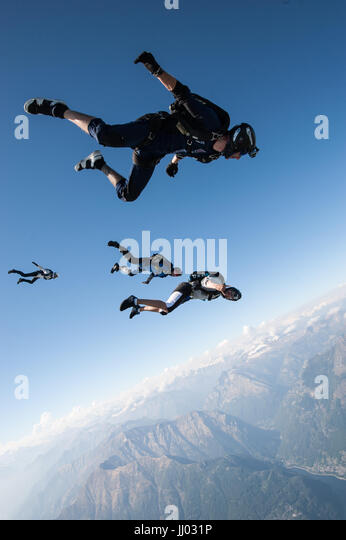 Four skydivers lining up on a tracking jump above Locarno, Switzerland with the Alps in the background - Stock Image