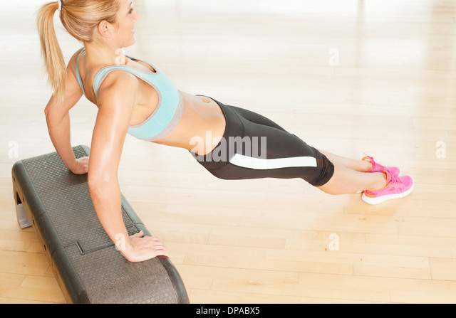 Woman stretching on step - Stock Image