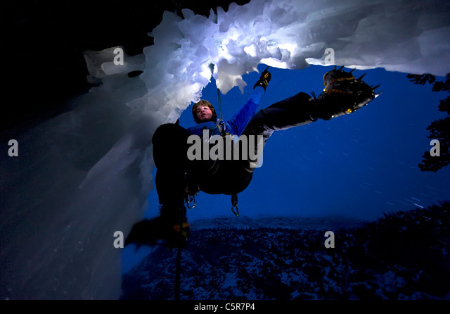 Ice Climbing at night on the edge of a cave. - Stock Image