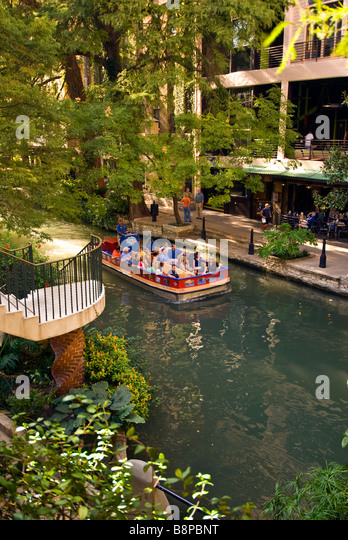 San Antonio River Walk riverwalk tour boat with tourists passes beside outdoor cafes and trees with bright green - Stock Image