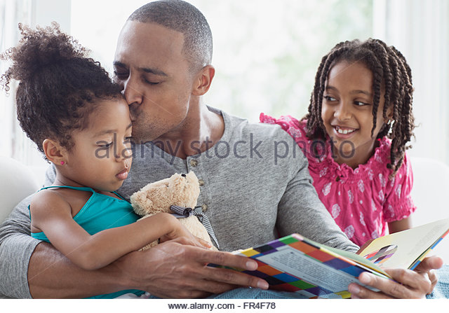 dad kissing youngest daughter during storytime - Stock-Bilder