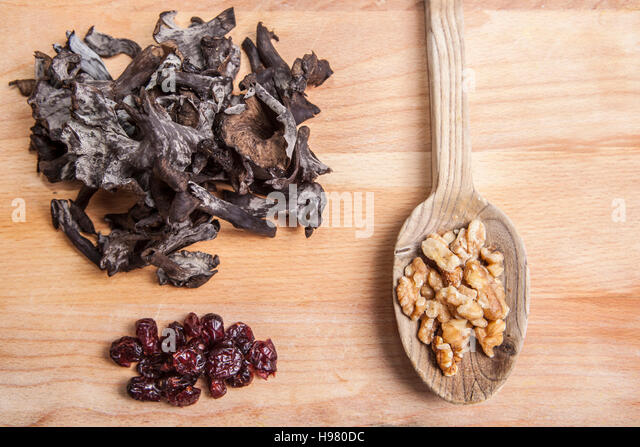 Horn of Plenty mushrooms over chopping board with wooden spoon full of walnut and blueberry - Stock Image