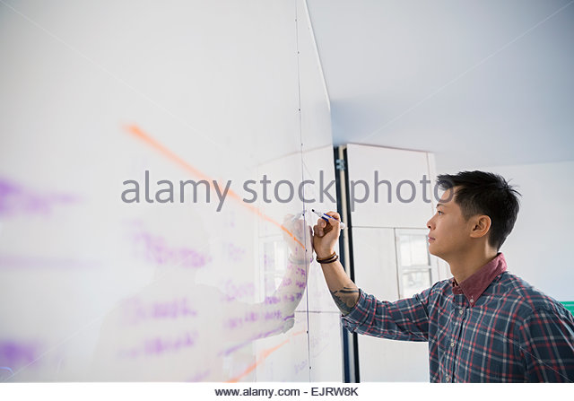 Businessman writing on whiteboard - Stock-Bilder