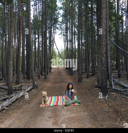 A young girl and her dog sit on a picnic blanket in the middle of the woods. - Stock Image