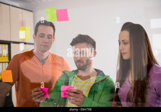 Colleagues planning deciding using post-its - Stock Image