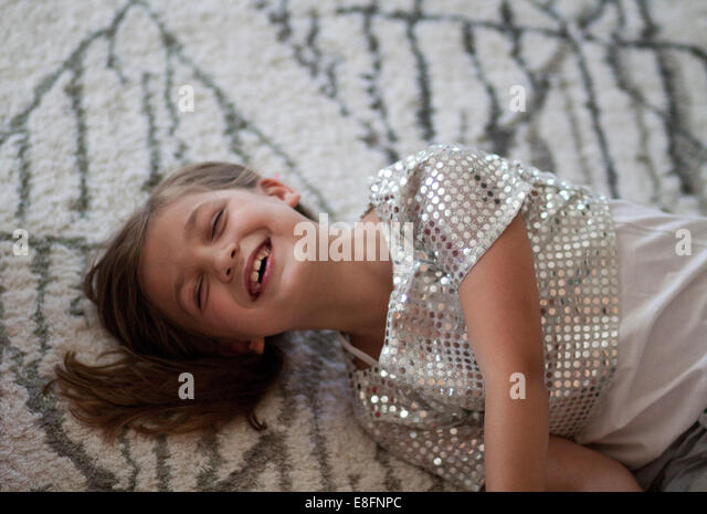 Girl (6-7) lying on carpet - Stock-Bilder