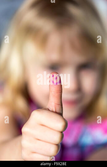 Little girl showing thumb up with smiling face - Stock Image