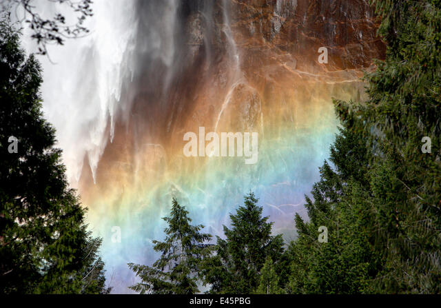 Sunlight creating a rainbow in the spray of the Bridalveil Falls, Yosemite National Park, California, USA, June - Stock Image
