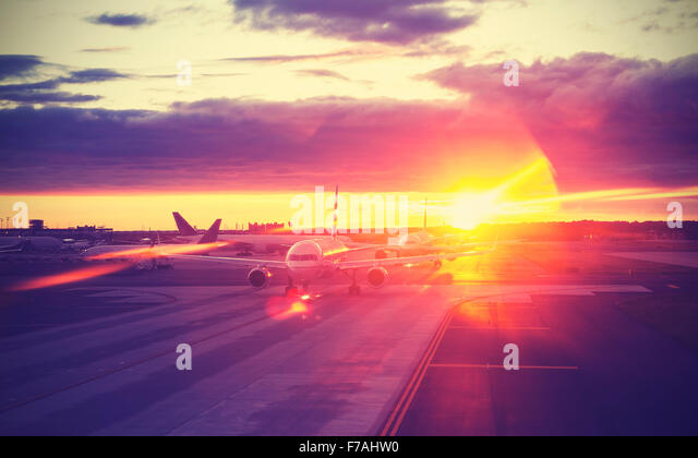 Vintage filtered picture of airport at sunset, travel concept, lens flare effect. - Stock-Bilder