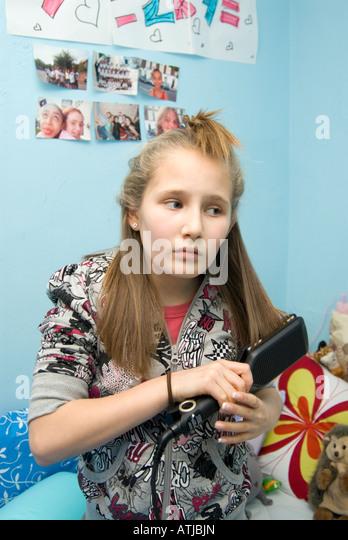 Girl using hair straighteners England UK - Stock-Bilder