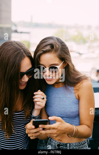 USA, New York City, two smiling friends looking at cell phone - Stock-Bilder