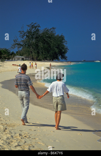 Seven Mile Beach couple walking beach early morning Grand Cayman Island - Stock Image
