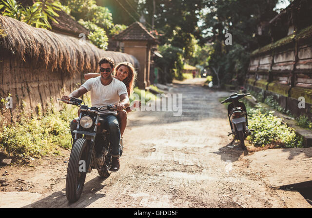 Shot of young couple on motorcycle on country road. Man riding on a motorbike with girlfriend on village road. - Stock Image