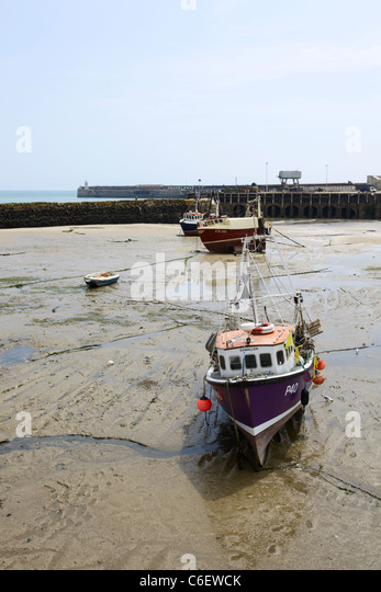 Boats beached on mud flats in Folkestone Harbour - Stock Image