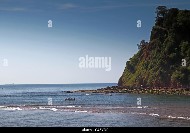 A rowing gig leaving the River Teign Estuary at Teignmouth passes Shaldon Ness headland, Devon, England, UK - Stock Image