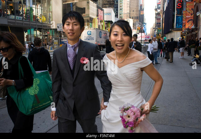 A newly married Asian couple celebrating their honeymoon in the area of Times Square. In the center of this spectacular - Stock Image