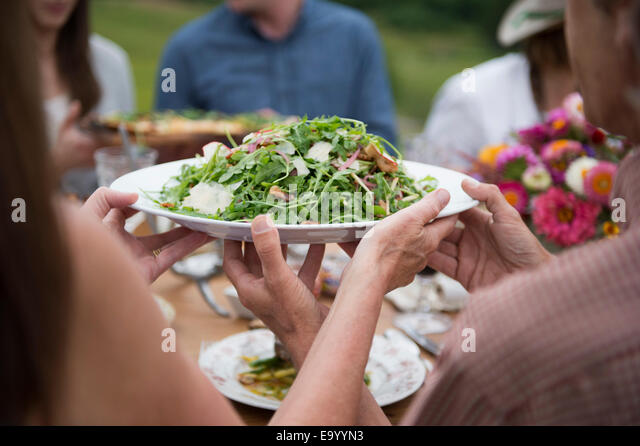 Group of adults enjoying meal, outdoors - Stock Image