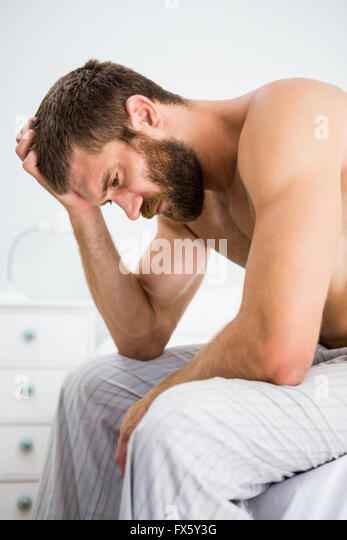 Depressed man with hand on head - Stock Image