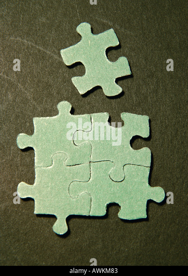 Four connected puzzle pieces and one separate piece, close-up - Stock Image