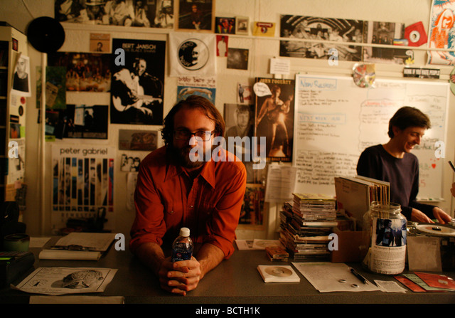 Heath, an owner of a small independent record store leans over the counter. - Stock-Bilder