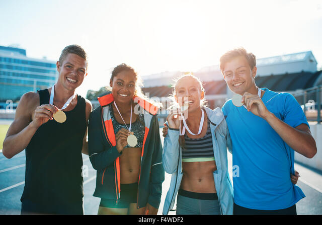 Portrait of ecstatic young runners showing medals. Young men and women looking excited after winner a running race. - Stock Image