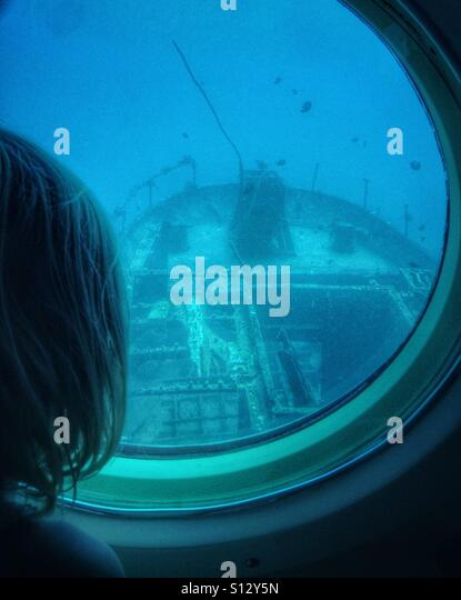 A girl views a sunken ship through the porthole of a submarine. - Stock Image