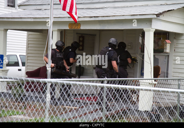 Police Tactical team serving high-risk narcotics related search warrant. - Stock Image