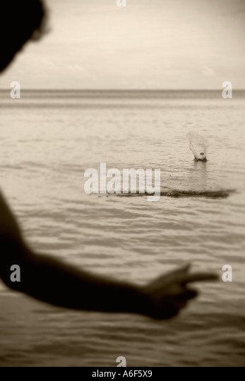 Harkening back to the freedom of a single and alone youth or adult male skips a splashing stone on Lake Ontario - Stock-Bilder