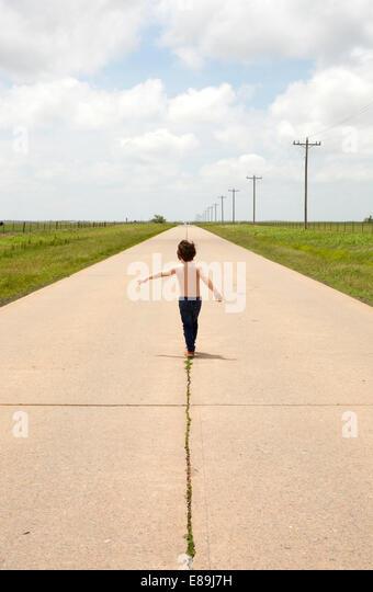 Boy walking along sidewalk in country - Stock-Bilder