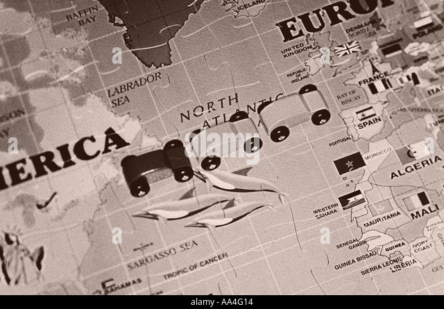 Wooden cars onn large world map puzzle - Stock Image