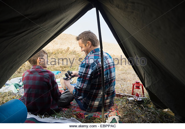Father and son with binoculars outside tent - Stock-Bilder