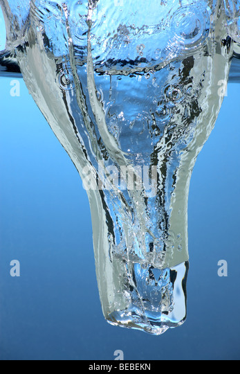 An Ice cube falling into water - Stock Image
