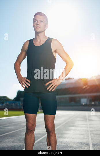 Fit young man standing with his hands on hips looking away. Determined male athlete preparing for a run on athletics - Stock Image
