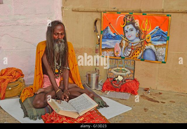 A Sadhu or Hindu saint reading the holy Gita with an image of Lord Shiva at back, Varanasi, Uttar Pradesh, India - Stock Image
