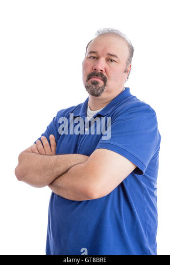 Portrait of a Serious Bearded Man in Blue Polo Shirt, Crossing his Arms and Looking at the Camera in an Aggressive - Stock Image