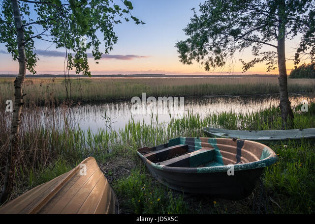 Scenic landscape with rowboats at peaceful summer evening in Hyvinkää, Finland. - Stock Image