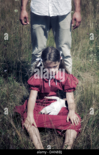 a sad girl sitting on a field, a man is standing behind her - Stock Image