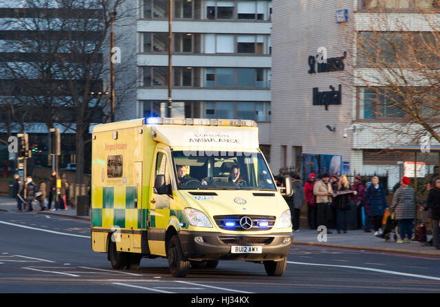 London Ambulance races past St Thomas' Hospital, London , England on an emergency call with blue lights illuminated. - Stock Image