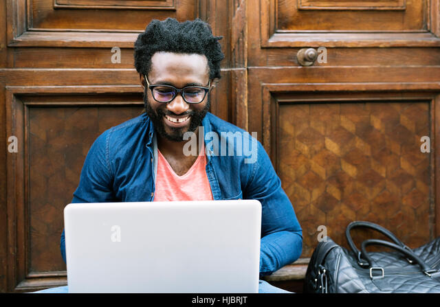 Portrait of african man sitting outside with laptop. Urban work Concept - Stock Image