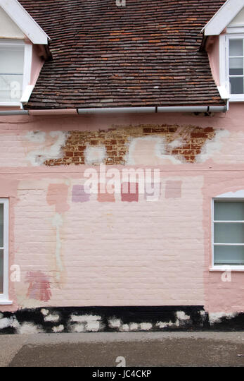 Pink Suffolk house wall prepared for painting with colour/color test  patches - Stock Image