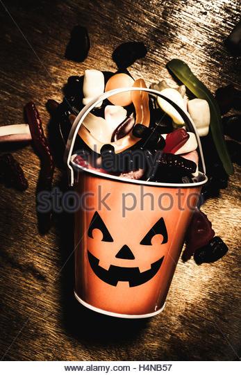 Cute dark halloween scene of a jack o lantern candy collector tin scattered in fun seasonal style. Fall of Halloween - Stock Image