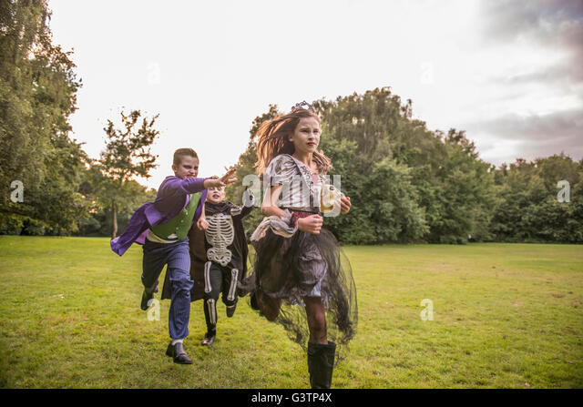 Children chase a girl dressed as a zombie prom queen for Halloween Night. - Stock Image