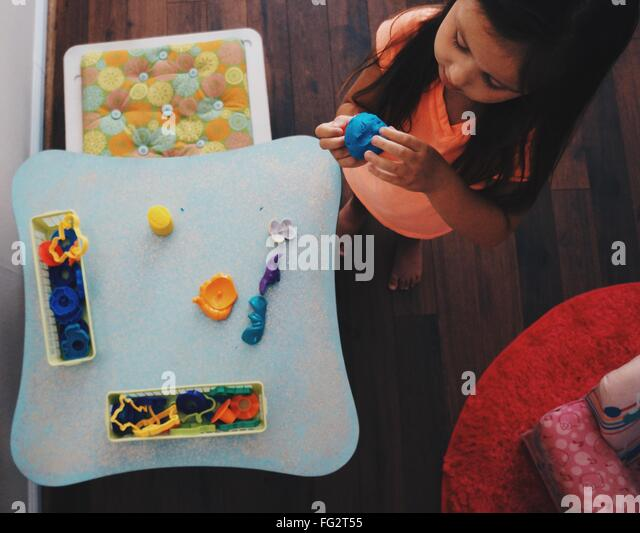 High Angle View Of Girl Making Clay Sculptures In House - Stock Image