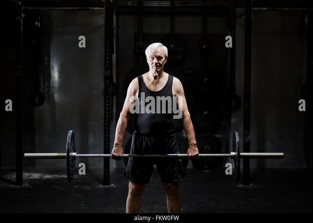 Senior man weightlifting barbell in dark gym - Stock Image