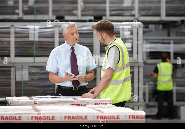 Warehouse worker and manager discussing order in engineering warehouse - Stock Image