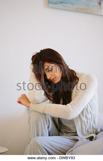 Young woman sitting in bed - Stock Image