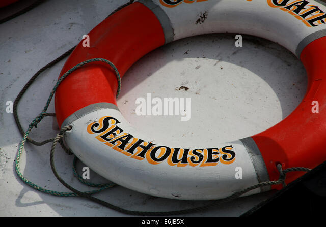 Red and white lifering at Seahouses port docks Northumbria , England UK - Stock Image